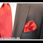 Rotes, unifarbenes Einstecktuch in Rosettenfaltung bei einem karierten Business-Anzug mit passender Krawatte